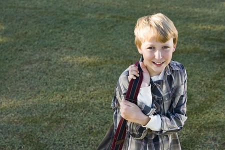 11 years: Boy (11 years) carrying school backpack, looking at camera smiling