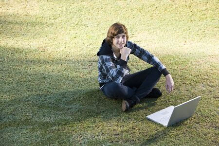 Boy, 15 years, online on his laptop in the park Stock Photo - 8167733