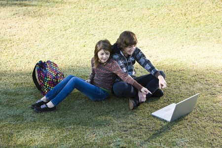 Boy and girl sitting on grass, online, pointing to the laptop screen photo