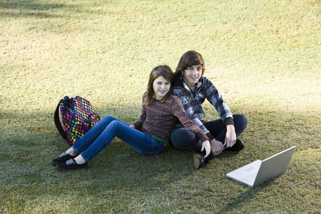 Boy and girl sitting on grass with laptop, online in park photo