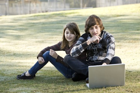 Boy and girl sitting on grass with laptop, online in park Stock Photo - 8167698