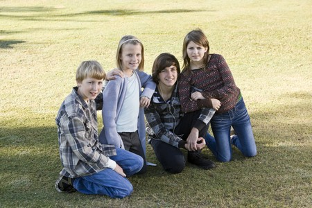 Four children (10 to 15 years) posing together on grass photo