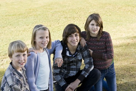 10 15 years: Four children (10 to 15 years) posing together on grass Stock Photo