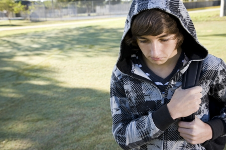 15: Teenage student (15 years) carrying bookbag on shoulder, looking down with serious expression Stock Photo