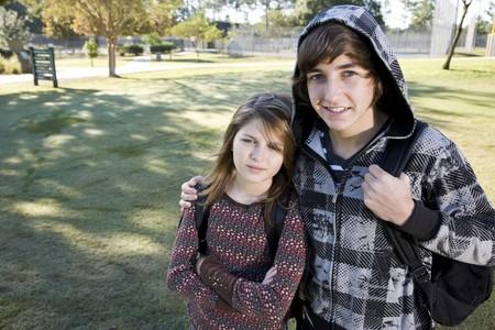 学校で bookbags と妹 (11 歳) の周りの腕を持つ 10 代の少年 (15 年)