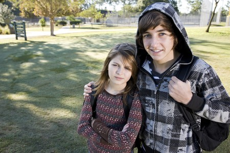 Teenage boy (15 years) with arm around younger sister (11 years), with bookbags at school photo