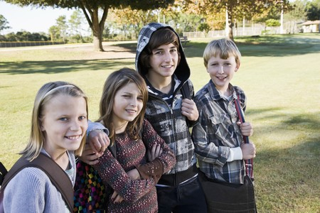 Four children (10 to 15 years) posing together with school bookbags photo