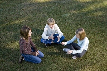 Three friends (10 to 11 years) sitting together on grass chatting photo