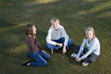 Three friends (10 to 11 years) sitting together on grass Banco de Imagens