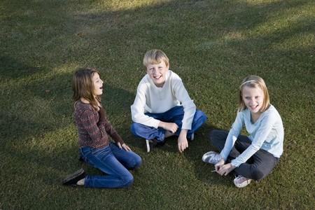 ni�os platicando: Tres amigos (de 10 a 11 a�os) sentados juntos sobre c�sped  Foto de archivo