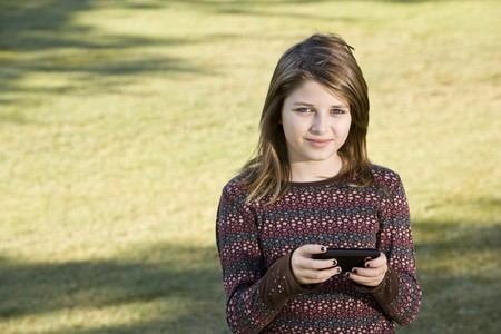 Girl (11 years) outdoors on grass holding camera Stock Photo - 8167686