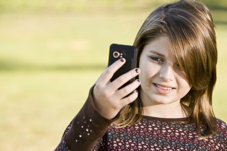 11 years: Girl (11 years) outdoors on grass holding camera Stock Photo