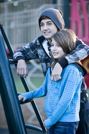 Teenage boy (15 years) with arm around younger sister (11 years) by playground equipment photo