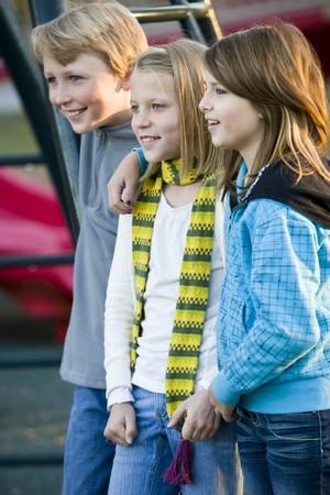 Drei Kinder (10-11 Jahre) stehen zusammen auf Spielplatz am kalten Tag Lizenzfreie Bilder - 8167681