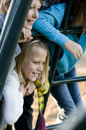 11 years: Children (10 and 11 years) leaning on playground equipment, watching and smiling Stock Photo