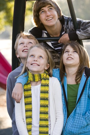 Group of children (10 to 15 years) standing together on playground on chilly day photo