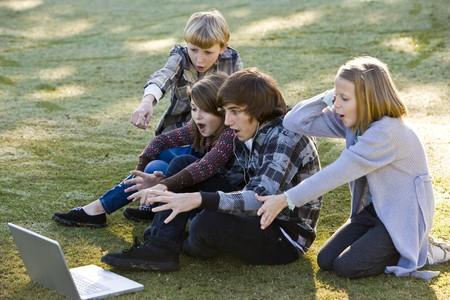 ショックを受けて、ラップトップ コンピューターに魅了されて子供たち (10 ~ 15 年) のグループ