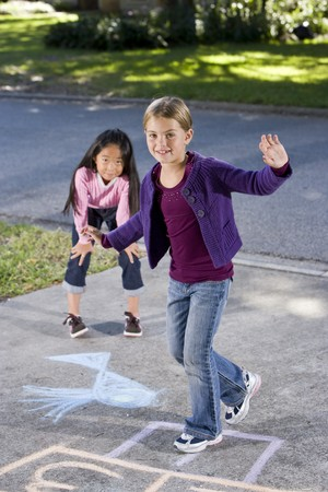 Multiracial friends having fun playing hopscotch on driveway Stock Photo - 8167816
