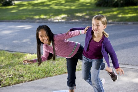 Two happy friends playing  on driveway - girls 7 years