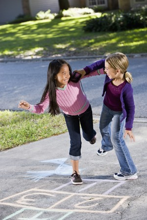 driveways: Multiracial friends having fun playing hopscotch on driveway