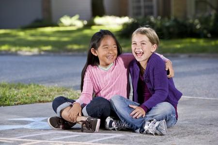 7 年間、私道笑って一緒に座っている二人の女の子 写真素材