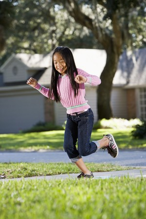 hopping: Smiling Asian girl, 7 years, playing on driveway outside house Stock Photo