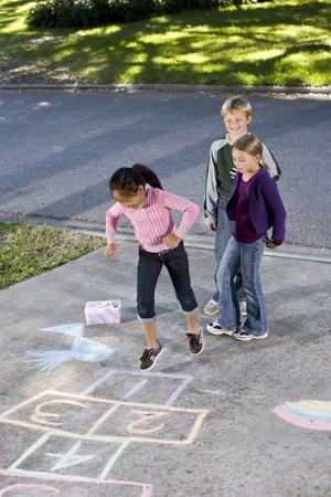 アジアの女の子は石けり遊びボード上を見てお友達とジャンプします。7 年 9 の男の子の女の子。