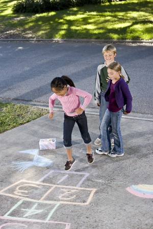 Asian girl jumping on hopscotch board with friends watching.  Girls 7 years, boy 9.