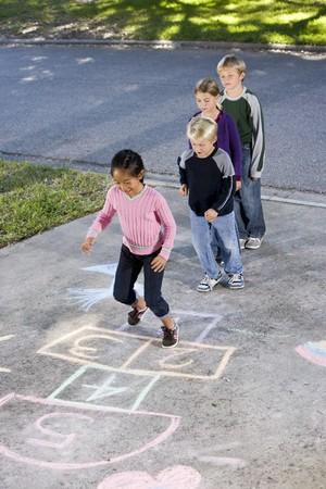 アジアの女の子は石けり遊びボード上を見てお友達とジャンプします。年齢 7 に 9