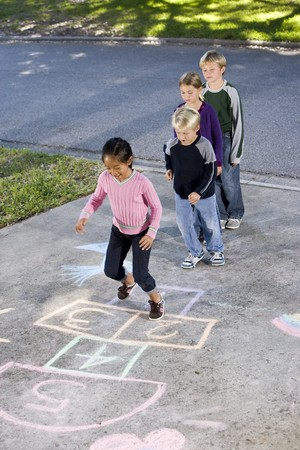 Asian girl jumping on hopscotch board with friends watching.  Ages 7 to 9 스톡 콘텐츠