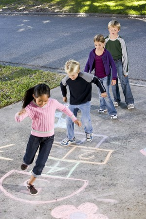 Children lined up on driveway, playing hopscotch.  Ages 7 to 9. photo