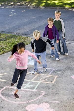 hermanos jugando: Ni�os que se alinearon en la v�a de acceso, jugar Rayuela. 7 A 9 a�os de edad.