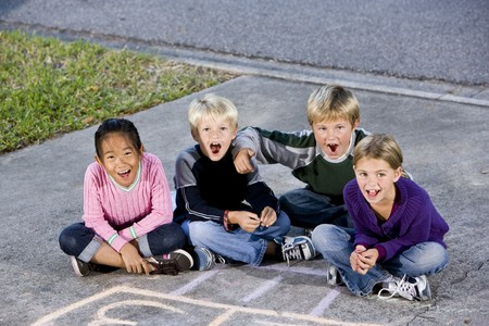 Four kids ages 7 to 9 sitting together on drive laughing and shouting Archivio Fotografico