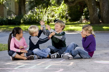Children playing, teasing and laughing on driveway, ages 7 to 9. photo