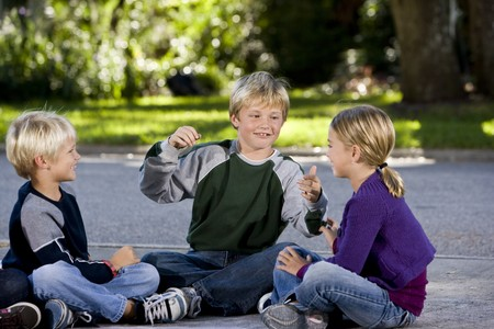 Three kids sitting on driveway playing, smiling and talking.  Ages 7 to 9 Stock Photo
