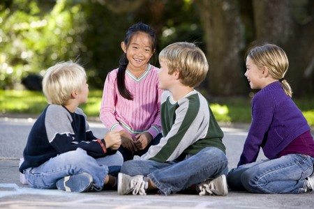 children talking: Four multi-ethnic children sitting together smiling outdoors, ages 7 to 9, focus on Asian girl
