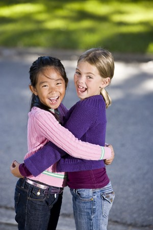 Two girls, 7 years, hugging and laughing Stock Photo
