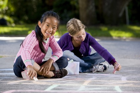 Two girls, 7 years, drawing pictures on driveway with chalk 스톡 콘텐츠