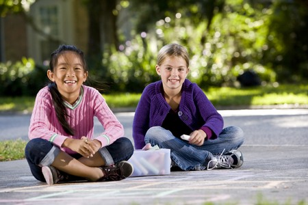 multiracial children: Two girls, 7 years, drawing pictures on driveway with chalk Stock Photo