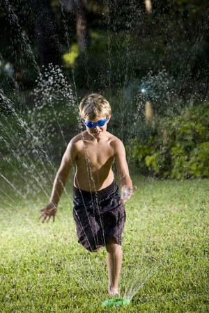 Boy, 9 years, wearing swim goggles and swimsuit getting soaked in lawn sprinkler photo