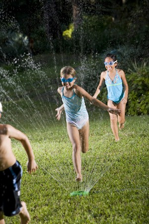 lawn sprinkler: Girls, 7 years, in swimsuits playing and splashing in sprinkler, focus on girl in middle Stock Photo