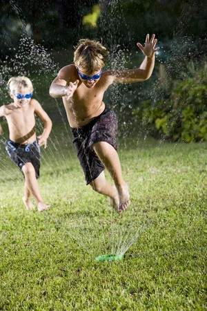 Focus on boy, 9 years, jumping through water spray from lawn sprinkler photo