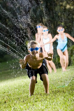 Happy boy (7 years) soaked by lawn sprinkler, friends in background Stock Photo