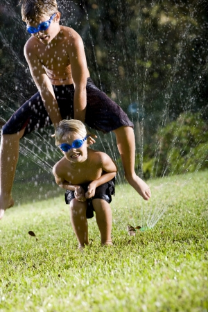 Children having fun getting wet and playing leapfrog, ages 7 and 9 photo
