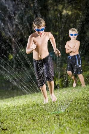 少年は、9 年間、流れる水スプレーの芝生のスプリンクラーから