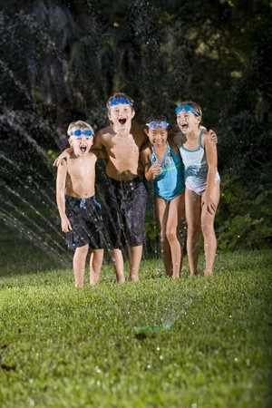 Four happy kids standing arm in arm shouting and laughing, soaked by lawn sprinkler