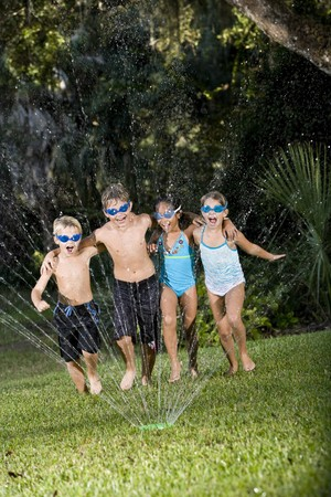 Four happy kids running arm in arm shouting and laughing, soaked by lawn sprinkler