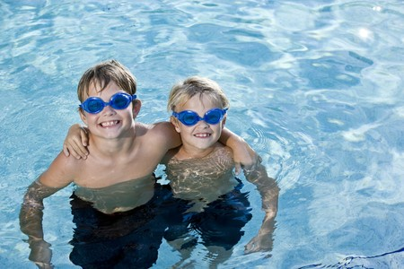Boys, 7 and 9 years, in pool wearing swim goggles, smiling photo