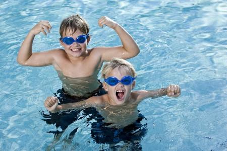 男の子は、7 歳から 9 歳、笑みを浮かべて、スイミング プールで叫んでいます。