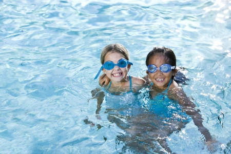 multiracial children: Two girls, 7 years, wearing swim goggles playing together in swimming pool